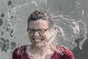 water splashing on face with glasses